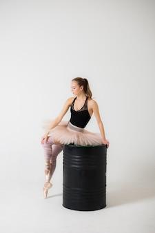 Ballerina in un bellissimo abito seduto su un primo piano barile nero