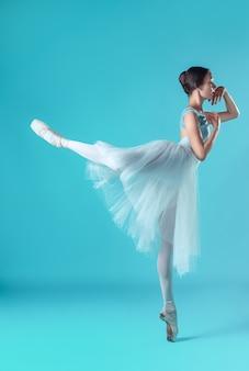 Ballerina in vestito bianco che posa sulle dita del piede, fondo dello studio.