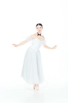 Ballerina in vestito bianco che posa sulle scarpe del pointe, bianco dello studio.