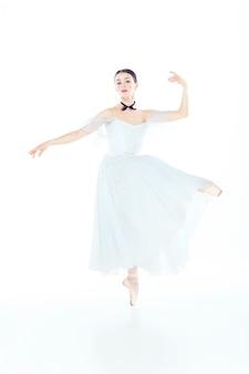 Ballerina in vestito bianco che posa sulle scarpe della punta, spazio dello studio.
