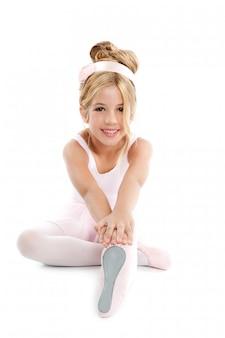 Ballerina poco balletto per bambini che si estende seduta