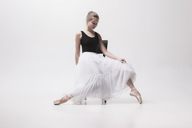 Ballerina teenager in gonna bianca che posa sulla sedia