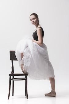 Ballerina teenager in gonna bianca che posa vicino alla sedia