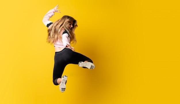 Ballerina urbana che balla sopra fondo giallo isolato e salto