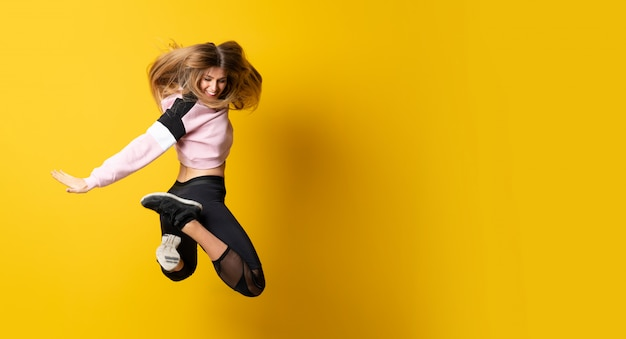 Ballerina urbana che balla su sfondo giallo isolato e saltare