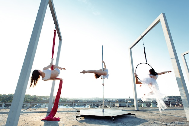 Ballerini atletici che eseguono danza aerea e pole sul tetto