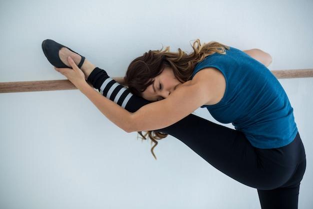 Ballerino che si estende su una sbarra mentre si pratica la danza