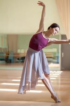Ballerino di balletto classico che propone alla sbarra sulla sala prove
