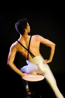 Ballerino di balletto maschio muscolare che si siede sotto i riflettori