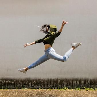 Ballerino femminile in cappa che salta contro il muro