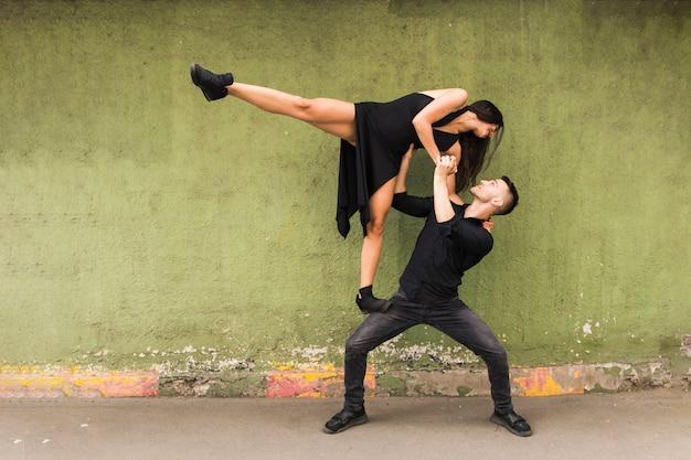 Ballerino maschio di tango che trasporta donna in vestito nero sulle sue ginocchia