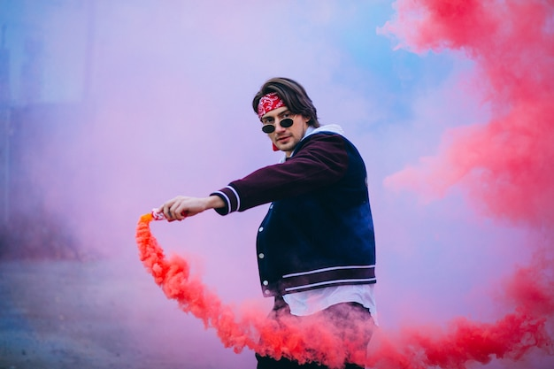 Ballerino urbano maschio con fumo colorato