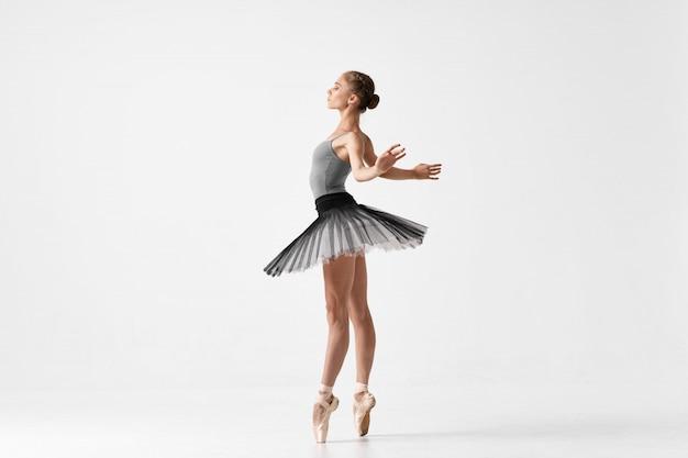 Balletto di dancing della ballerina della donna su una superficie leggera nello studio