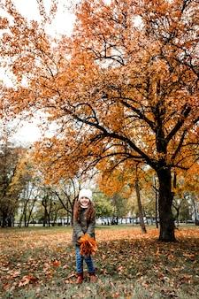 Bambina 5 anni divertendosi nella foresta di autunno
