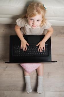 Bambina a casa che gioca sul computer portatile