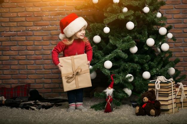 Bambina a natale con scatola regalo dall'albero di natale