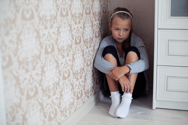 Bambina addolorata seduta nell'angolo della stanza