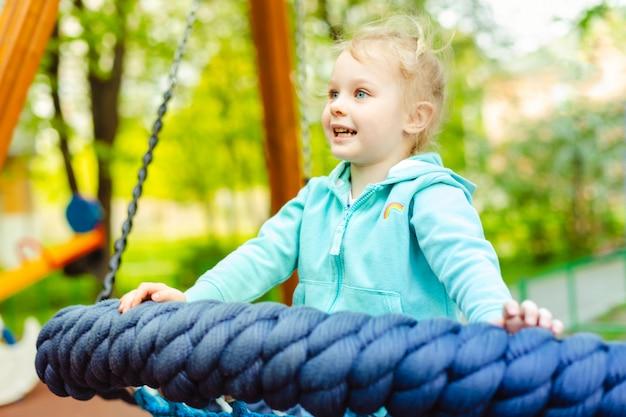 Bambina adorabile 4 anni divertendosi su un'oscillazione della corda rotonda in un campo da giuoco.