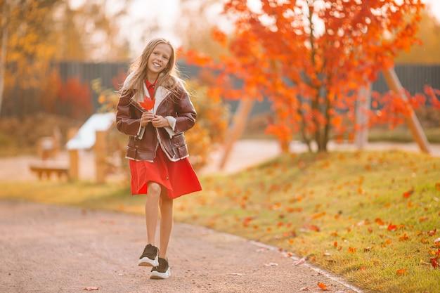 Bambina adorabile al bello giorno di autunno all'aperto