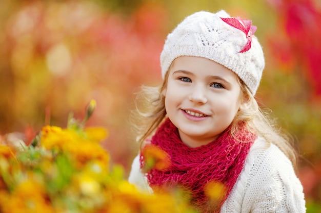 Bambina adorabile all'aperto al bello giorno di autunno. attività autunnali per bambini.