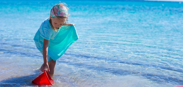 Bambina adorabile alla spiaggia bianca durante la vacanza tropicale