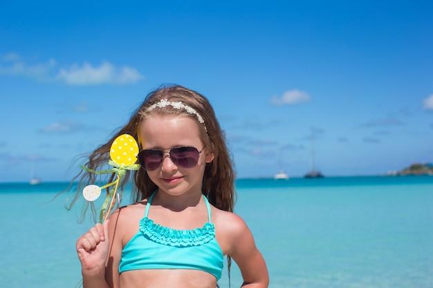 Bambina adorabile alla spiaggia bianca durante le vacanze estive