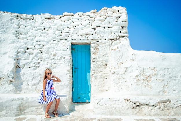 Bambina adorabile alla vecchia via del villaggio tradizionale greco tipico