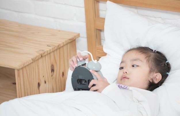 Bambina adorabile asiatica che mette sulla sveglia bianca della tenuta della mano del letto