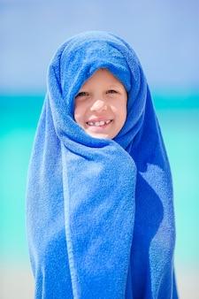 Bambina adorabile avvolta in asciugamano alla spiaggia tropicale dopo il nuoto nel mare