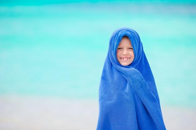 Bambina adorabile avvolta in asciugamano in spiaggia tropicale dopo il nuoto in mare