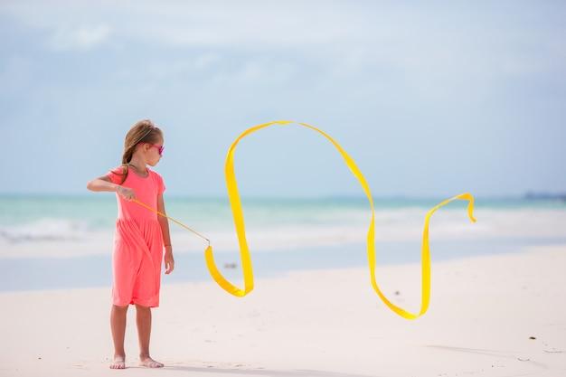 Bambina adorabile che balla con con il nastro relativo alla ginnastica