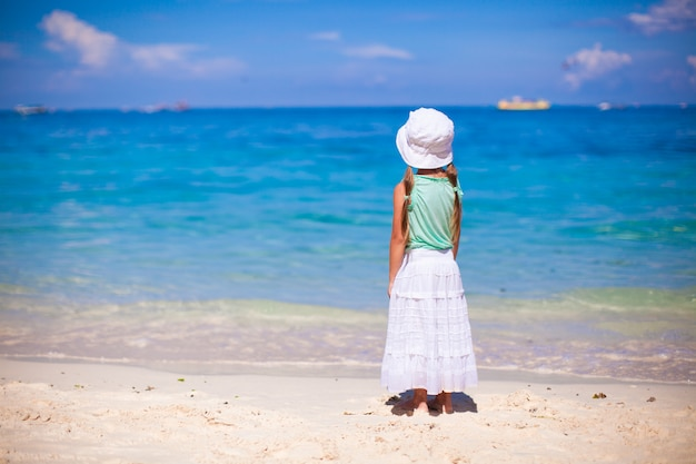 Bambina adorabile che cammina sulla spiaggia bianca tropicale