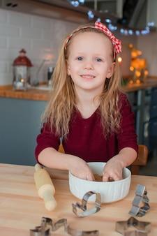 Bambina adorabile che cuoce i biscotti del pan di zenzero di natale