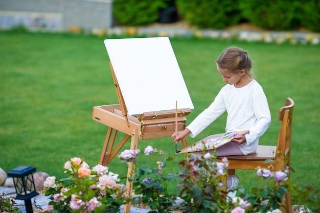 Bambina adorabile che dipinge un'immagine sul cavalletto all'aperto. piccola artista appassionata del suo hobby.