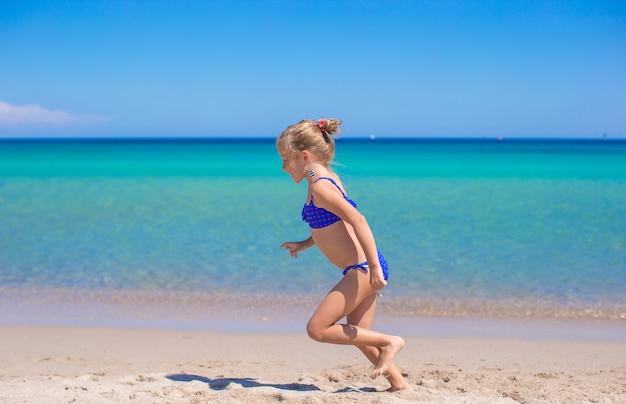 Bambina adorabile che fa ruota sulla spiaggia sabbiosa bianca tropicale