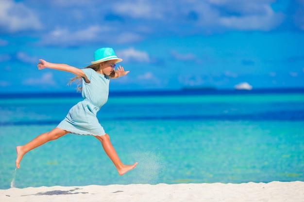 Bambina adorabile che funziona sulla spiaggia bianca tropicale