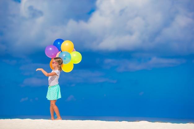 Bambina adorabile che gioca con gli aerostati alla spiaggia