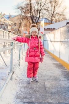 Bambina adorabile che gode del pattinaggio alla pista di pattinaggio sul ghiaccio