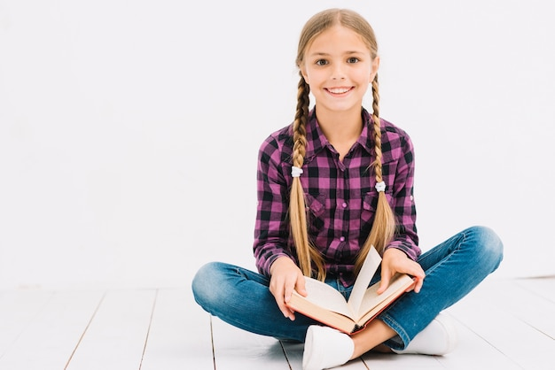 Bambina adorabile che legge un libro che si siede sul pavimento