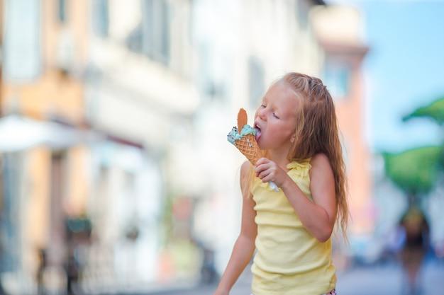 Bambina adorabile che mangia gelato all'aperto all'estate nella città