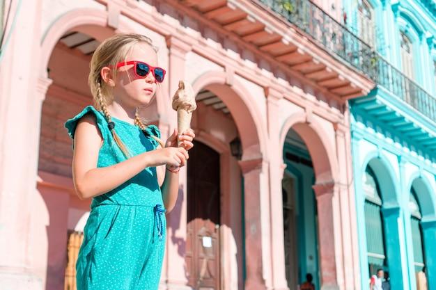 Bambina adorabile che mangia il gelato nell'area popolare a vecchia avana, cuba.