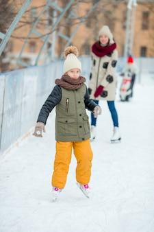 Bambina adorabile che pattina sulla pista di pattinaggio sul ghiaccio all'aperto