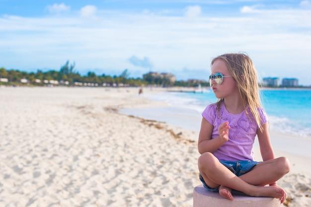 Bambina adorabile che si siede nella posizione di loto su una spiaggia esotica