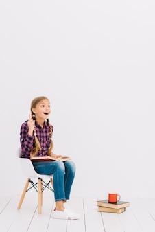 Bambina adorabile che si siede su una sedia che legge un libro