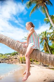 Bambina adorabile che si siede sulla palma durante le vacanze estive sulla spiaggia bianca