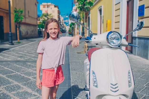 Bambina adorabile che sorride sul ciclomotore all'aperto