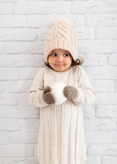 Bambina adorabile che tiene una palla della neve