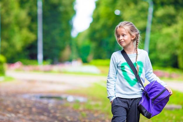 Bambina adorabile che va in palestra con la sua borsa sportiva