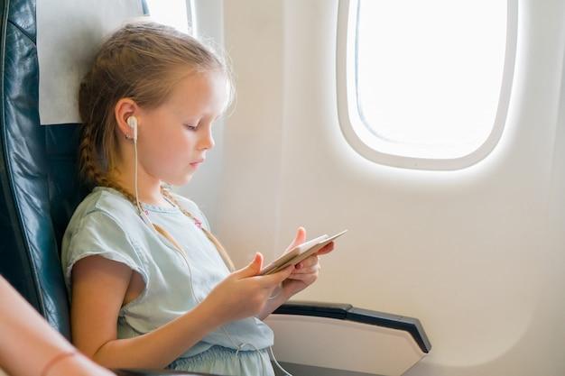 Bambina adorabile che viaggia in aereo. bambino sveglio con il computer portatile vicino alla finestra in aereo