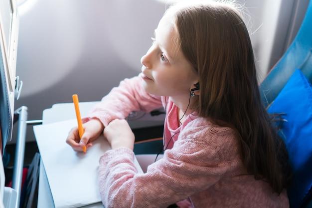 Bambina adorabile che viaggia in aereo. scherzi l'immagine del disegno con le matite variopinte che si siedono vicino alla finestra